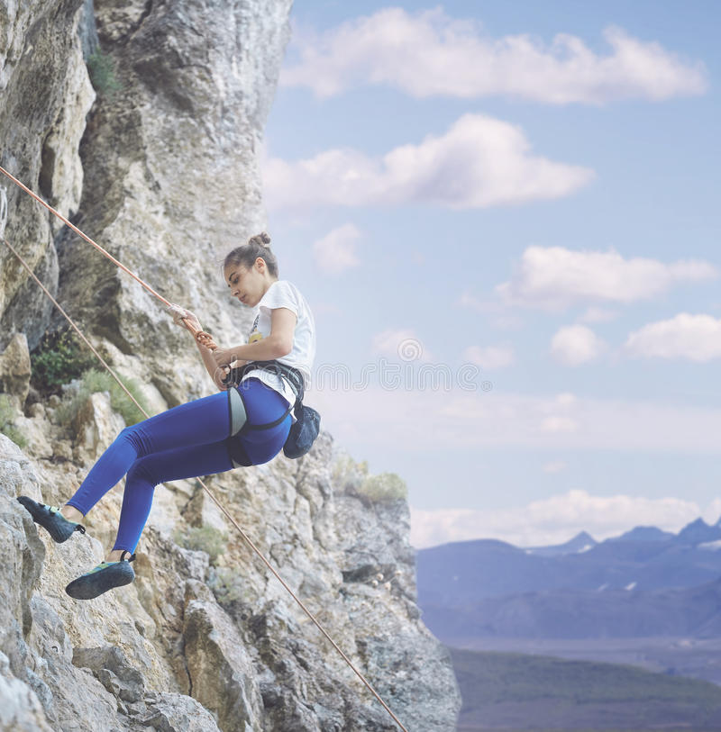 Woman rock climber on the cliff. Young cheerful woman climbs on the cliff. rock climber Learns to climb rocks on a rocky wall. woman makes hard move and looking stock photography