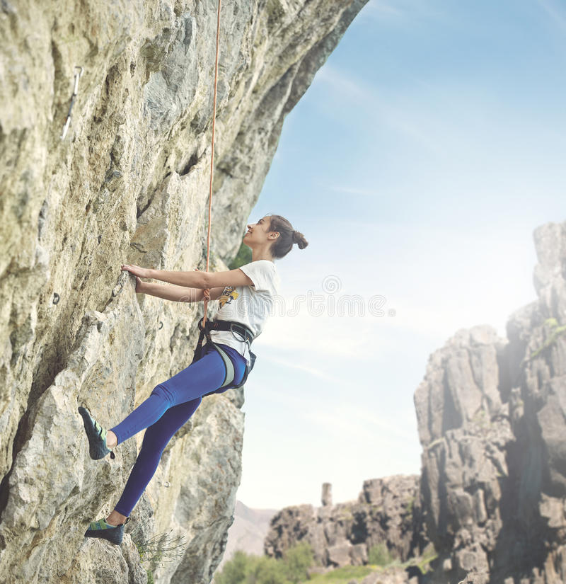 Woman rock climber on the cliff. Young cheerful woman climbs on the cliff. rock climber Learns to climb rocks on a rocky wall. woman makes hard move and looking royalty free stock photo