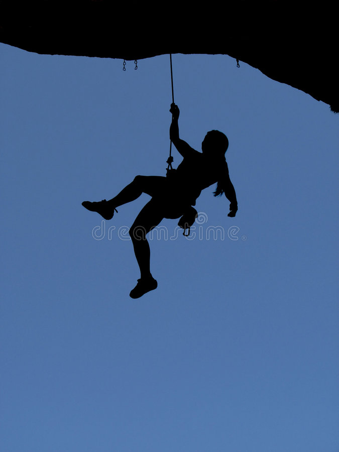 Woman rock climber silhouette. Silhouette of a woman rock climber being lowered off a steep overhanging climb with a blue sky background stock photo