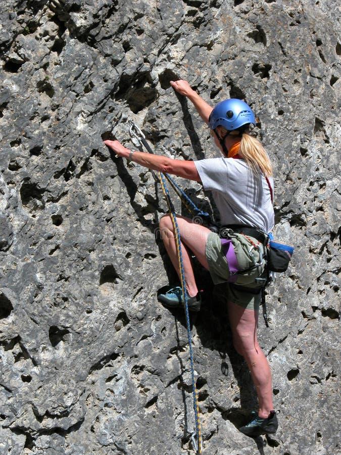 Woman rock climbing stock photos