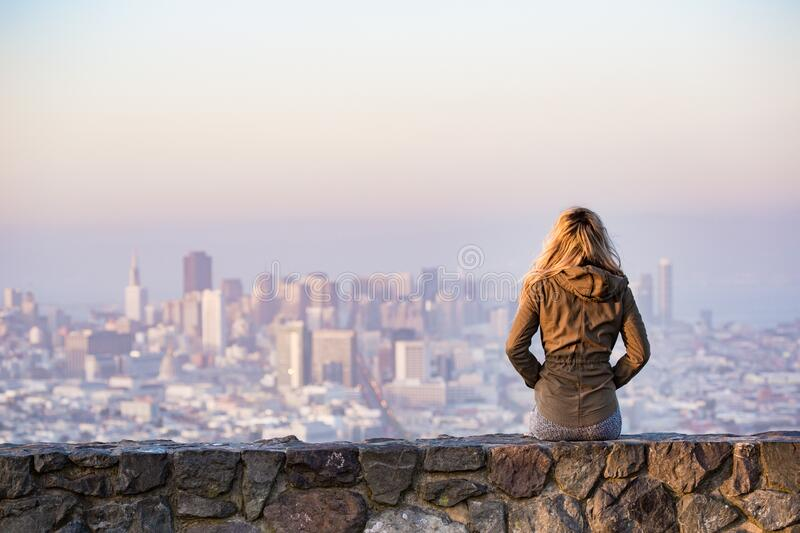 Woman on Rock Platform Viewing City royalty free stock photography