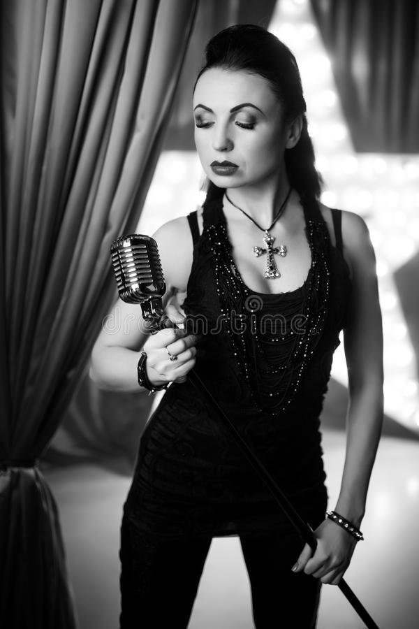 Woman rock star. Beautiful woman with long black hair, black jacket singing and holding big silver microphone. concert, style, fashion, music musician play pop stock images