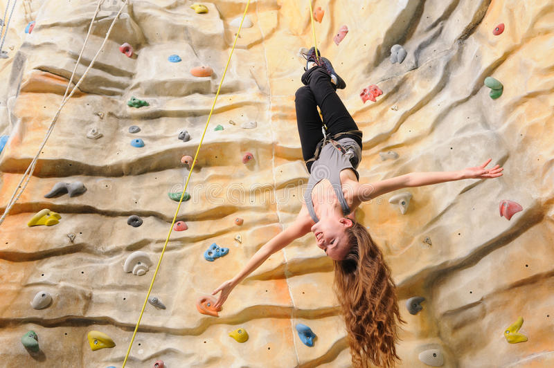 Woman on rock wal. Active young woman on rock wall in sport center stock images