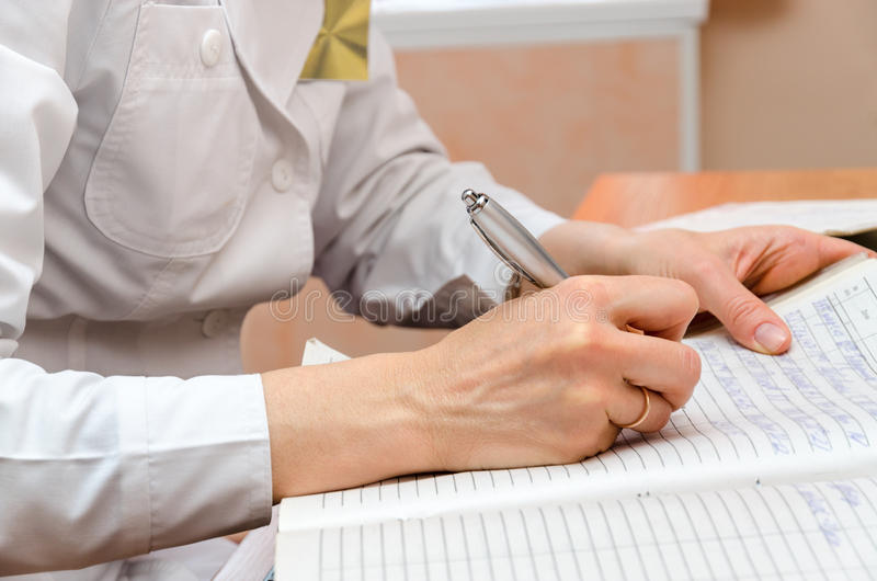 Woman-roentgenographer in polyclinic office writes patient data royalty free stock photo