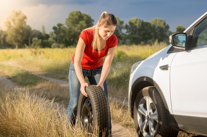 Young woman rolling spare wheel to change flate tyre on her car royalty free stock photos