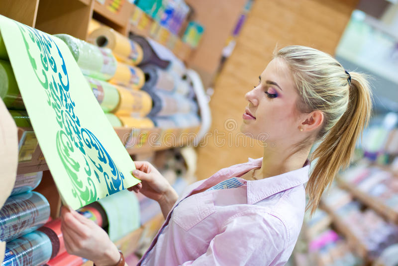 Woman with rolls of wallpaper. Young beautiful blond woman choosing among rolls of wallpaper in shop stock images