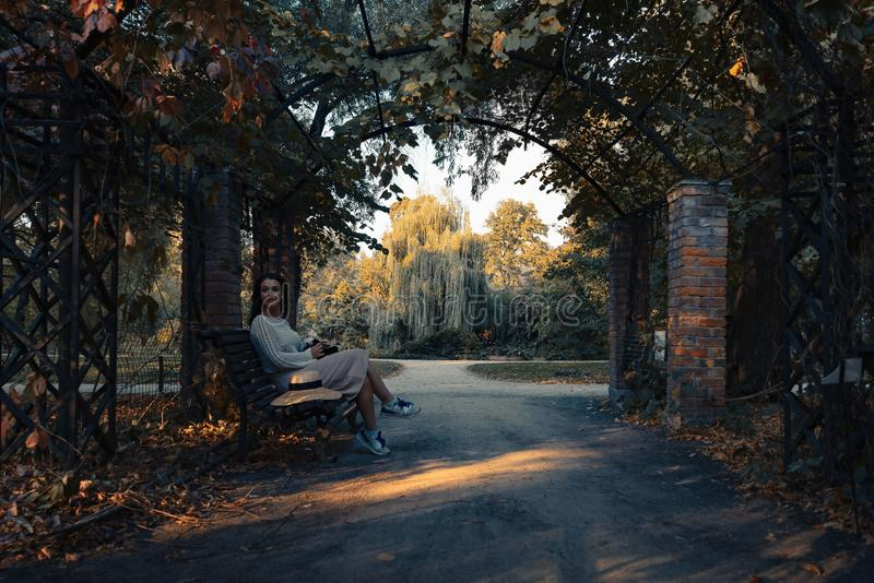 Woman in romantic attire relaxing outdoor in autumn park and enjoying good weather view on pond and sunset. royalty free stock photography