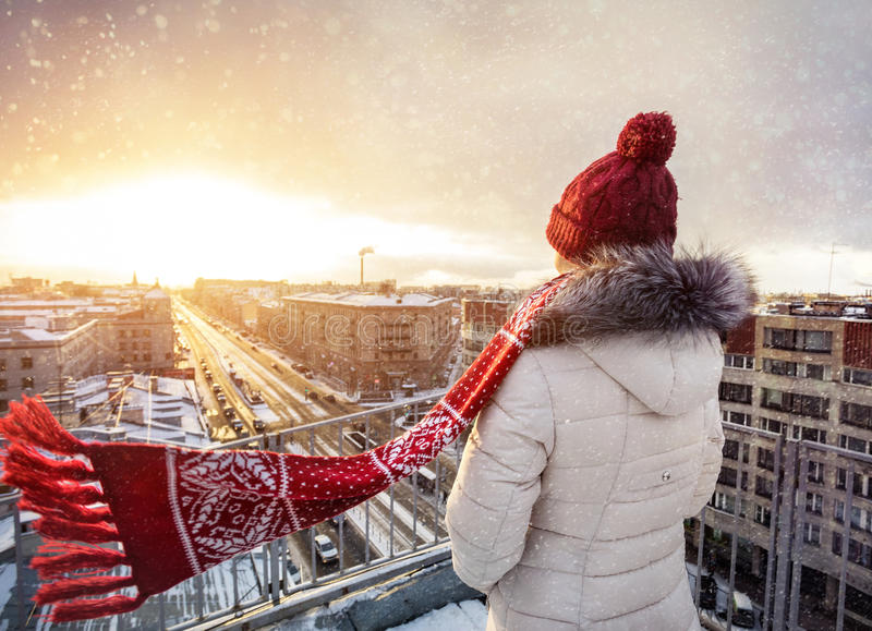 Woman on the roof in winter Petersburg. Woman in Christmas Hat and red scarf on the roof at snow fall in Saint Petersburg, Russia stock photo
