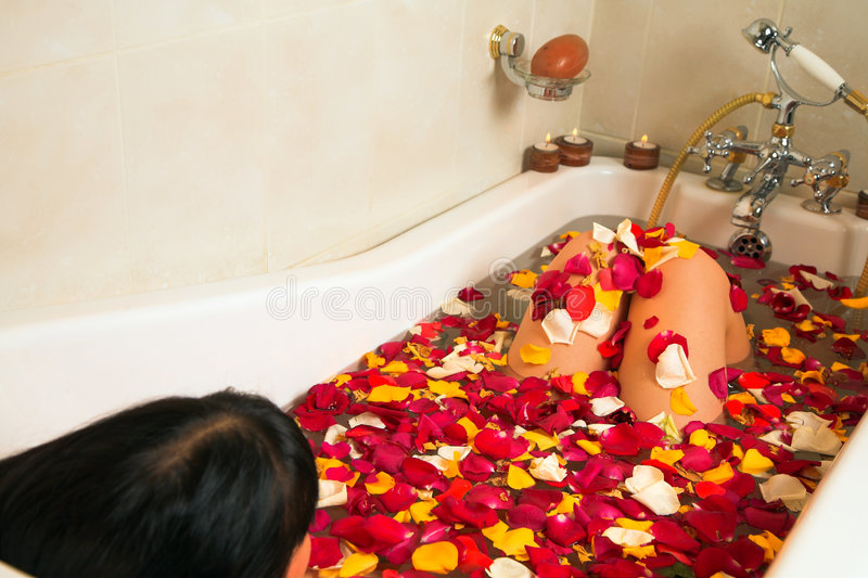 Woman in a rose petal bath royalty free stock images