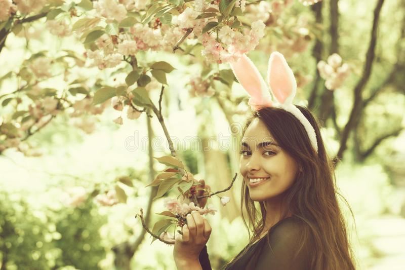 Woman smiling at tree with blossoming sakura flowers. Woman with rosy bunny ears and long, brunette hair smiling at tree with blossoming sakura flowers in spring stock photography