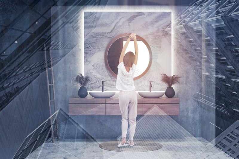 Woman in round mirror bathroom. Rear view of woman in pajamas standing in white and marble bathroom with double sink and round mirror. Toned image double royalty free stock images