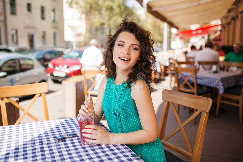 Woman in round sunglasses with cocktail at cafe terrace having fun stock photo