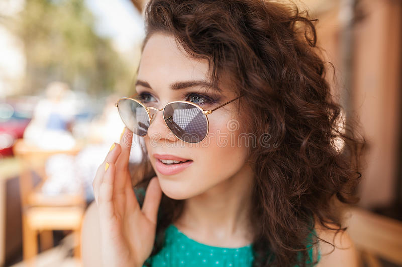 Woman in round sunglasses with cocktail making order at cafe terrace stock images