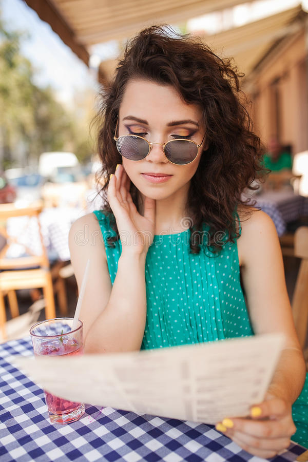 Woman in round sunglasses with cocktail making order at cafe stock image