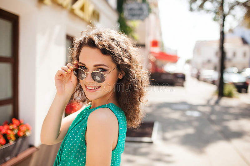 Woman in round sunglasses smiling over shoulder in city street stock photography