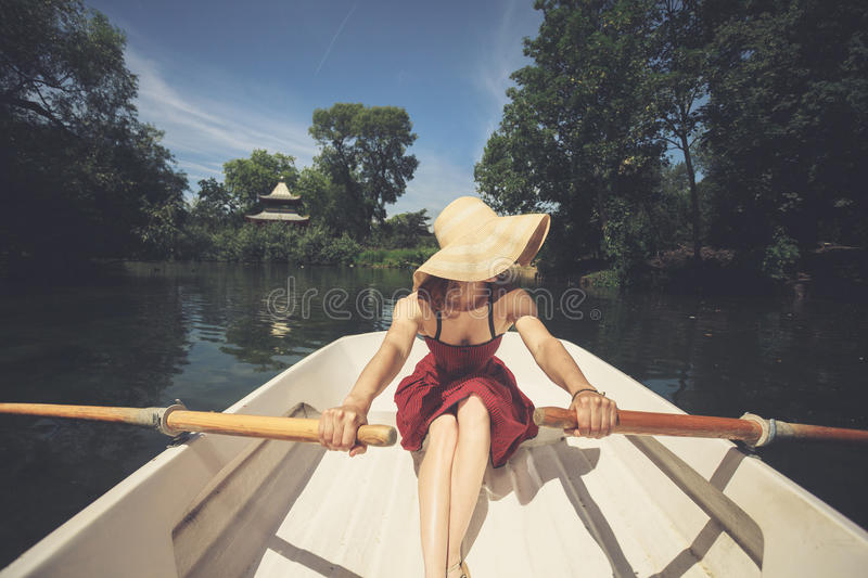 Woman rowing a boat in summer. A young woman is rowing a boat on a summer day stock image