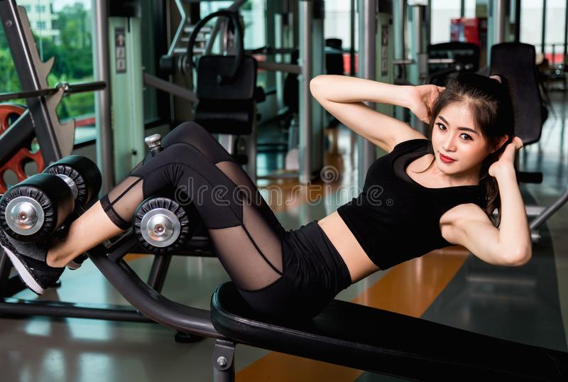 Woman on rowing machine and sit-ups on fitness gym. Beautiful young Woman on rowing machine and sit-ups on sport fitness gym stock photo