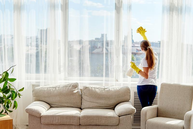 Woman in rubber gloves cleaning window with cleanser spray and yellow rag at home, copy space, back view. People, housework. stock photo