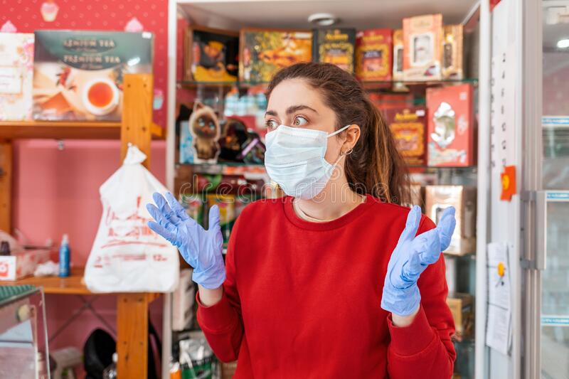 A woman in rubber gloves and a medical mask throws her hands out in fright. In the background-shelves and shop Windows. The. Concept of coronavirus, quarantine royalty free stock photography