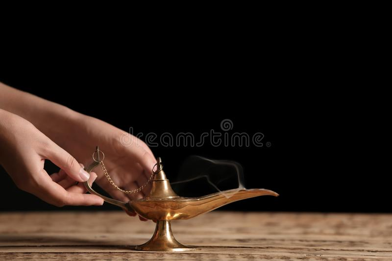 Woman rubbing magical Aladdin lamp stock photography