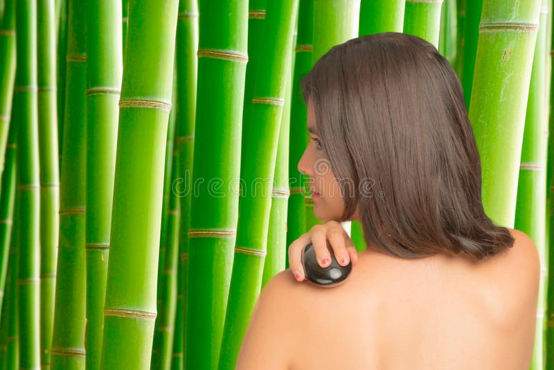 Woman rubbing with a massage stone stock photography