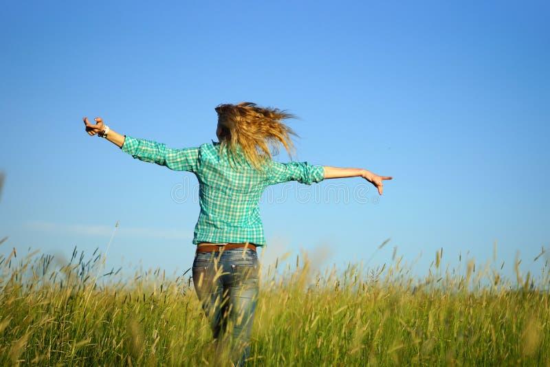 Woman run away through high grass. Pretty young woman run away through high grass royalty free stock images
