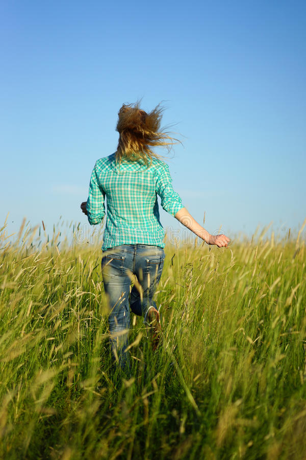 Woman run away through high grass. Pretty young woman run away through high grass stock photo