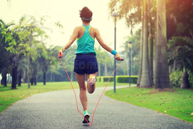 Runner athlete jumping rope at tropical park stock image