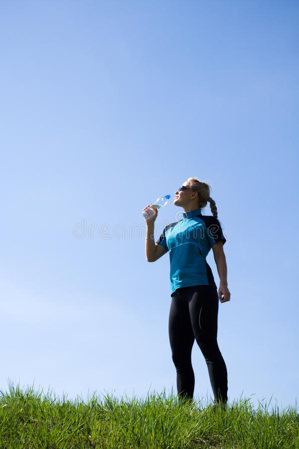 Woman runner drinking water after running stock image