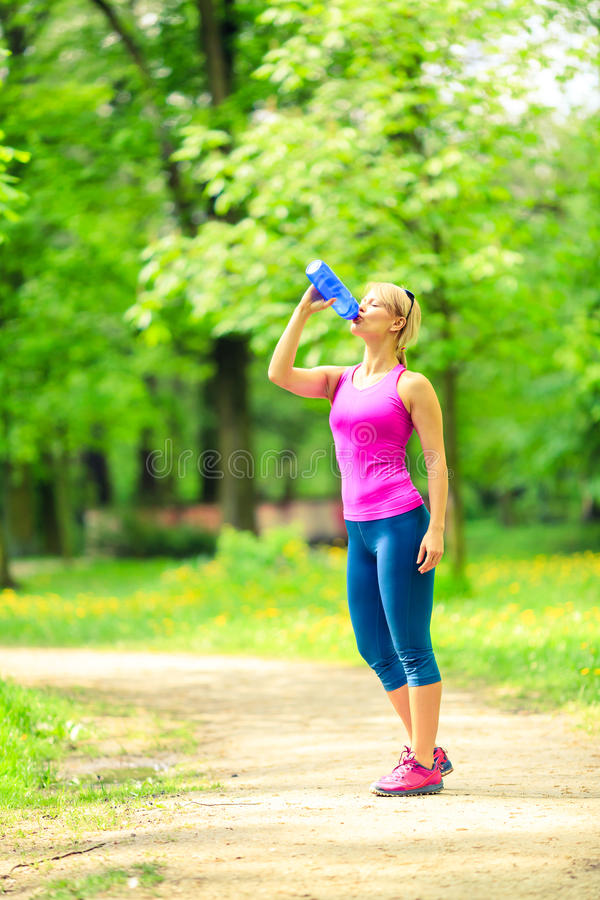 Woman runner drinking water on training stock photos