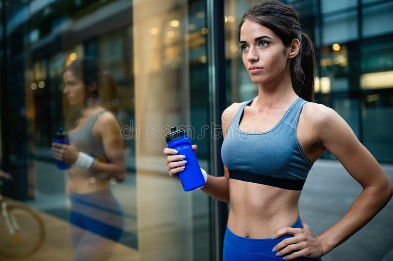 Woman runner is having a break and drinking water royalty free stock images