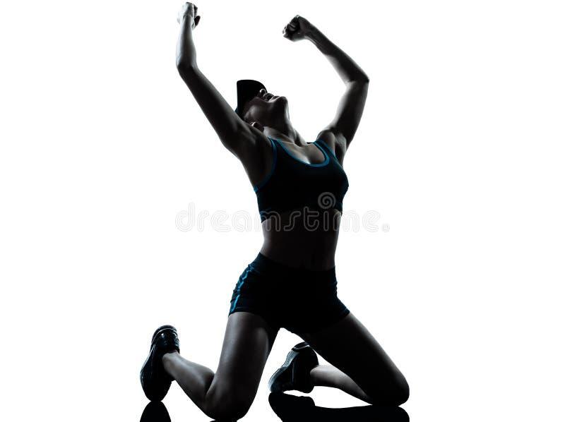 Woman runner jogger kneeling winner victory stock photo