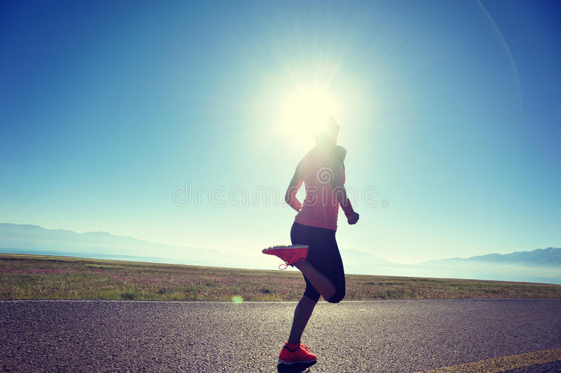 Woman runner running on sunrise seaside trail. Young fitness woman runner running on sunrise seaside trail royalty free stock photography