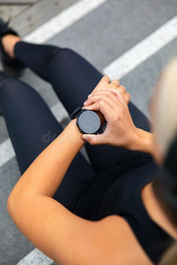 Woman runner setting up the fitness smart watch for running stock image