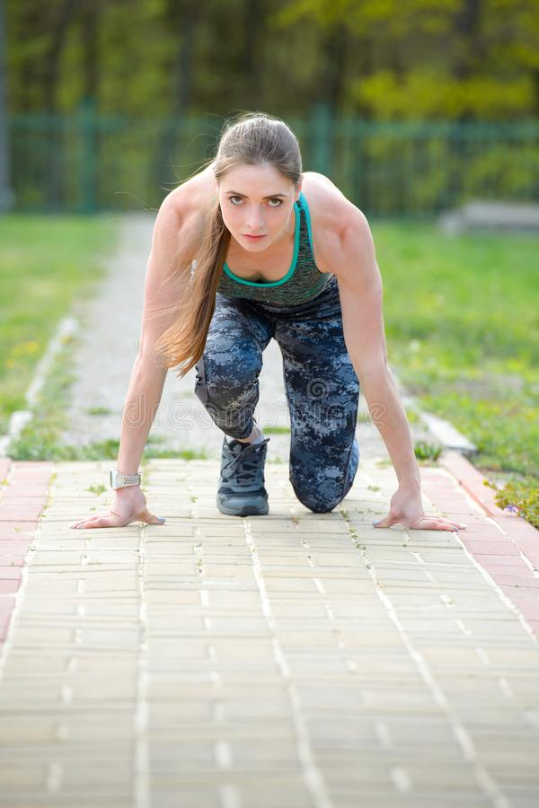 Woman runner on start position at stadium. Runner in start pose on running surface. Woman run outdoor at running track. Sport and stock photography