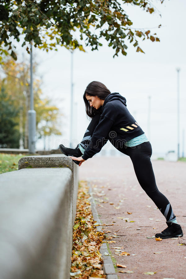 Woman runner stretching legs before run. stock images