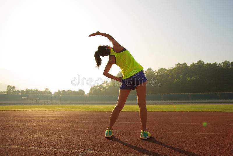 Woman runner stretching on stadium track. Young fitness woman runner stretching on stadium track royalty free stock image