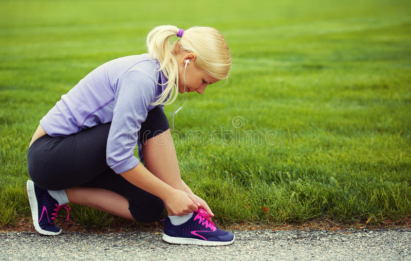 Woman runner tying running shoes. Blonde Girl over Grass stock photo