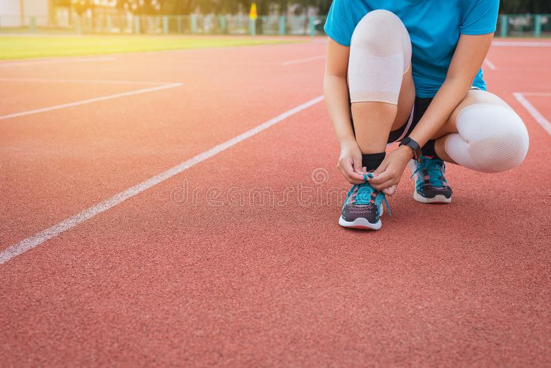 Woman runner tying shoelace on running track,Athlete to tie her shoes. Woman runner tying shoelace on running track,Athlete female to tie her shoes stock photos