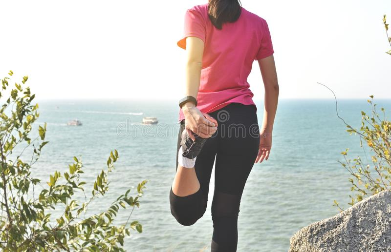 Woman runner warm up before taking a jogging on beach stock photos