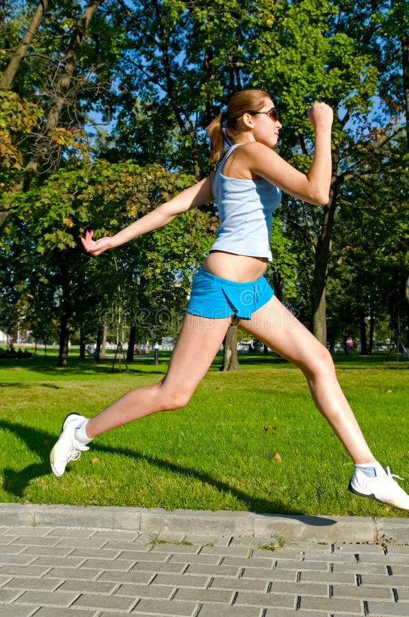 Woman running. Young woman running in the park royalty free stock photography