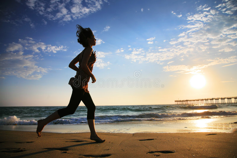 Woman running. Girl at the beach running by the ocean at sunset stock images