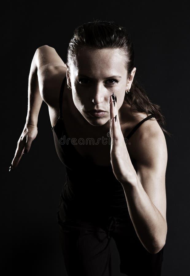 Woman running. Over dark background