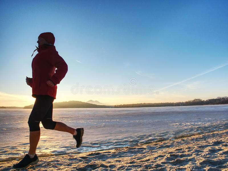Woman running along shore of a frozen lake in winter spring. Young woman running along the shore of a frozen lake in winter spring. Regular training run, keep royalty free stock photos