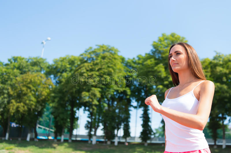 Woman running on arena track. Coach or trainer at workout. Runner on competition and future success. Girl sunny outdoor on blue sky. Sport and healthy fitness royalty free stock photography