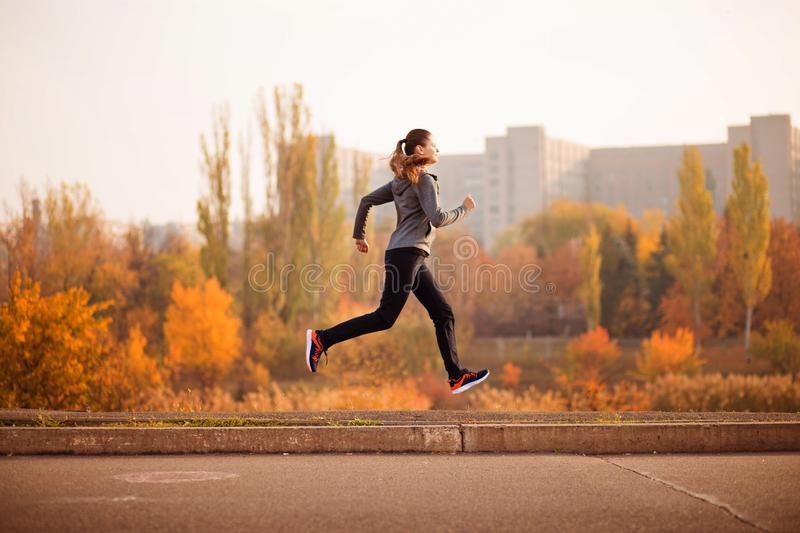 Woman running in autumn fall forest. Healthy concept royalty free stock images
