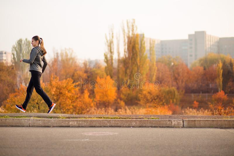Woman running in autumn fall forest. Healthy concept stock photo