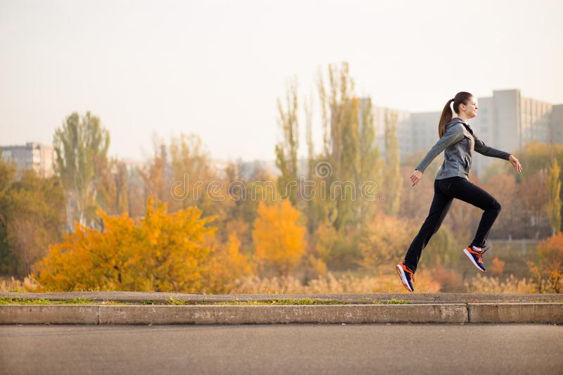 Woman running in autumn fall forest. Healthy concept royalty free stock photo