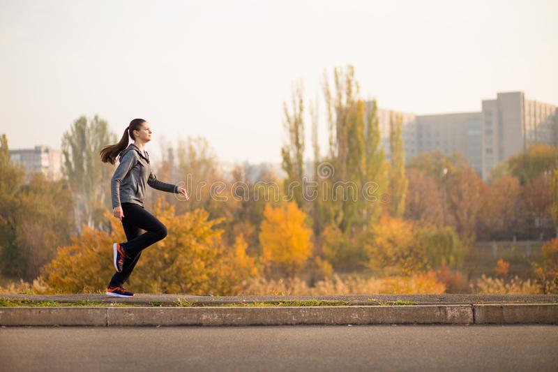 Woman running in autumn fall forest. Healthy concept royalty free stock image