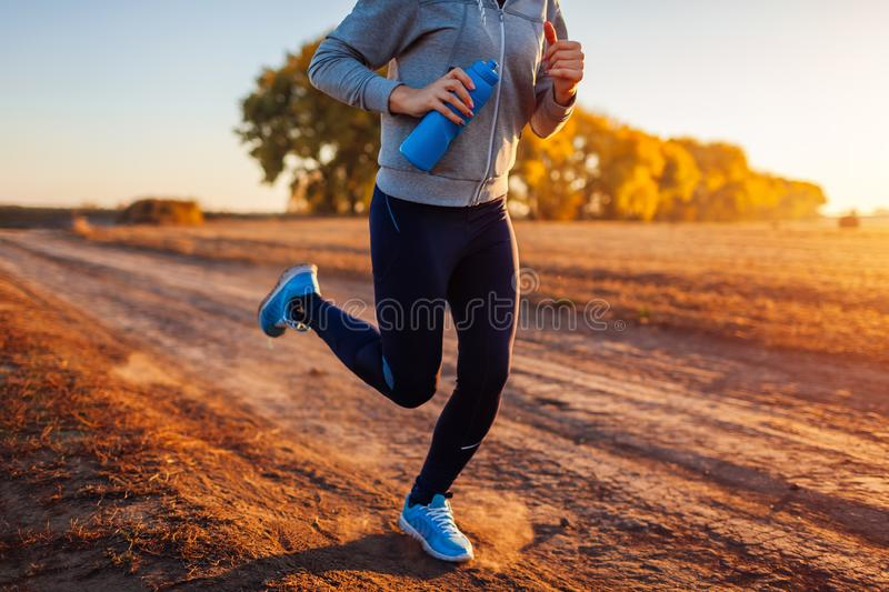 Woman running in autumn field at sunset. Healthy lifestyle concept. Active sportive people. Close up of legs royalty free stock image